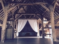 A stunning rustic barn with our fairy-light canopy and white curtains.