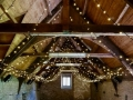 This is Mells Barn in Somerset, a 15th century communal space with our fairy-light canopy installed prior to a wedding.
