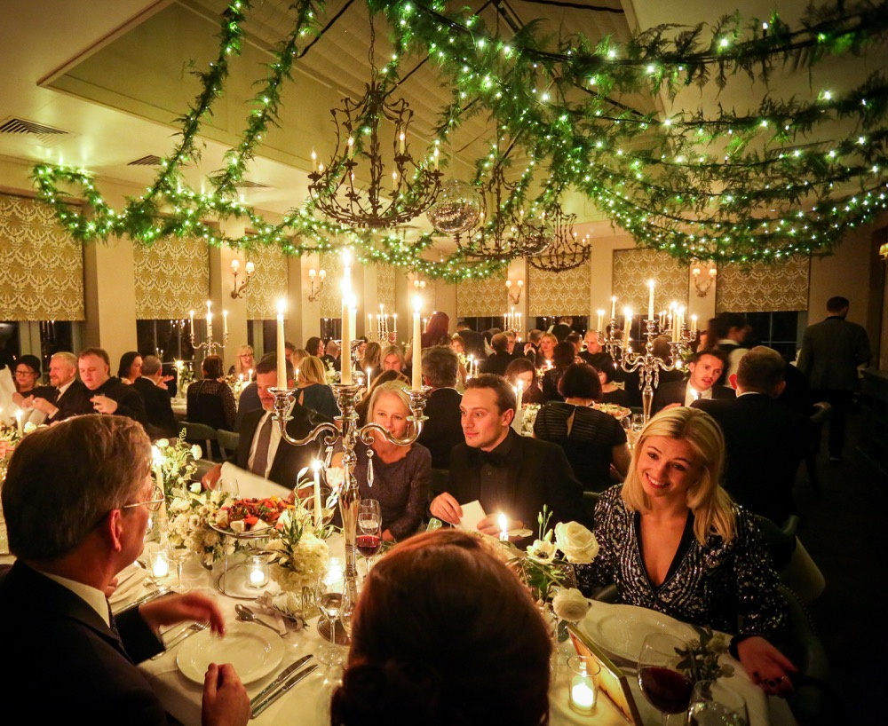 Image of fairy-light chains with foliage jnside a dining room with people eating