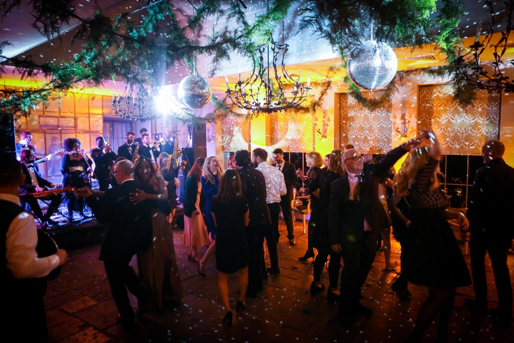 Image of the Orangery at Babington House with a band playing, people dancing and Mirrorball's shining.