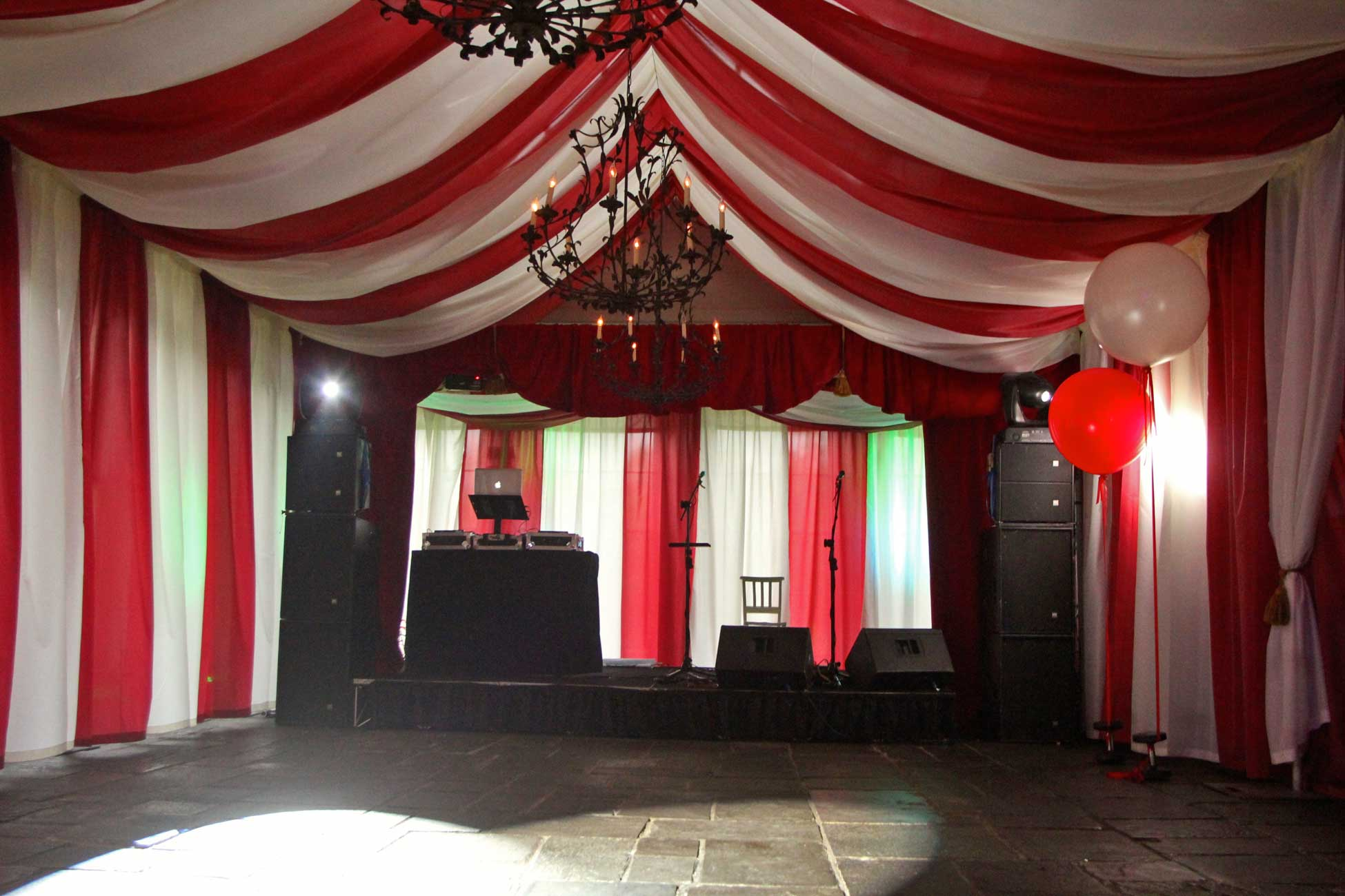 Image of a circus themed party with big top, stage and dj decks