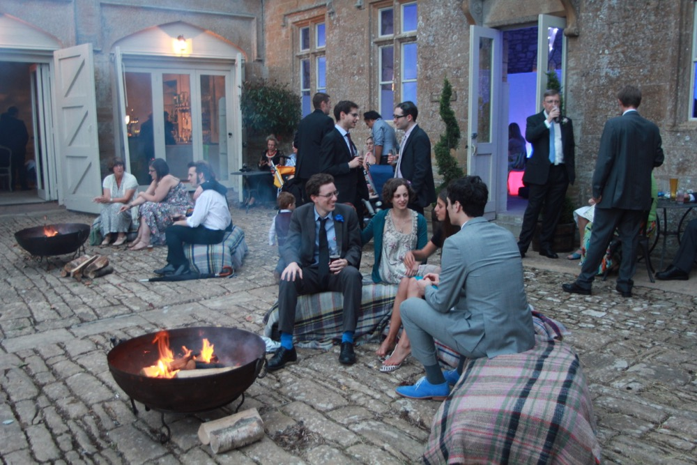 Image of people sitting around a fire pit at a wedding