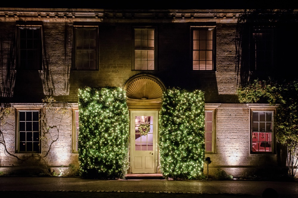 Image of the front of Babington House with the large bushes light.