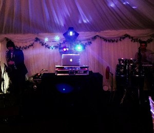 Image of DJ decks with sax player and percussionist
