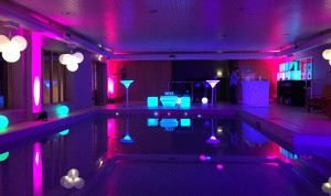 Image of a swimming pool decorated for a birthday party with creative lighting and furniture.