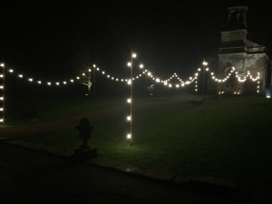 Image of string lights running up to the entrance of a church for a winter wedding.