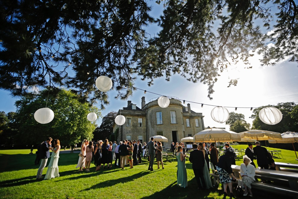 Image of Babington House in the summer with wedding guests and tree lighting.