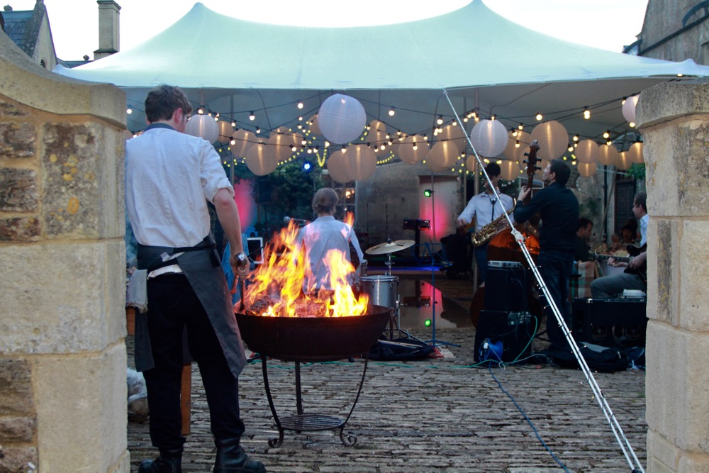 Image of a stretch marquee with fire-pit cooking food
